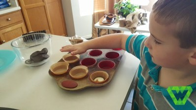 Parker helping put in the cupcake liners