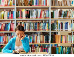 """Portrait of clever student with open book reading it in college library"""