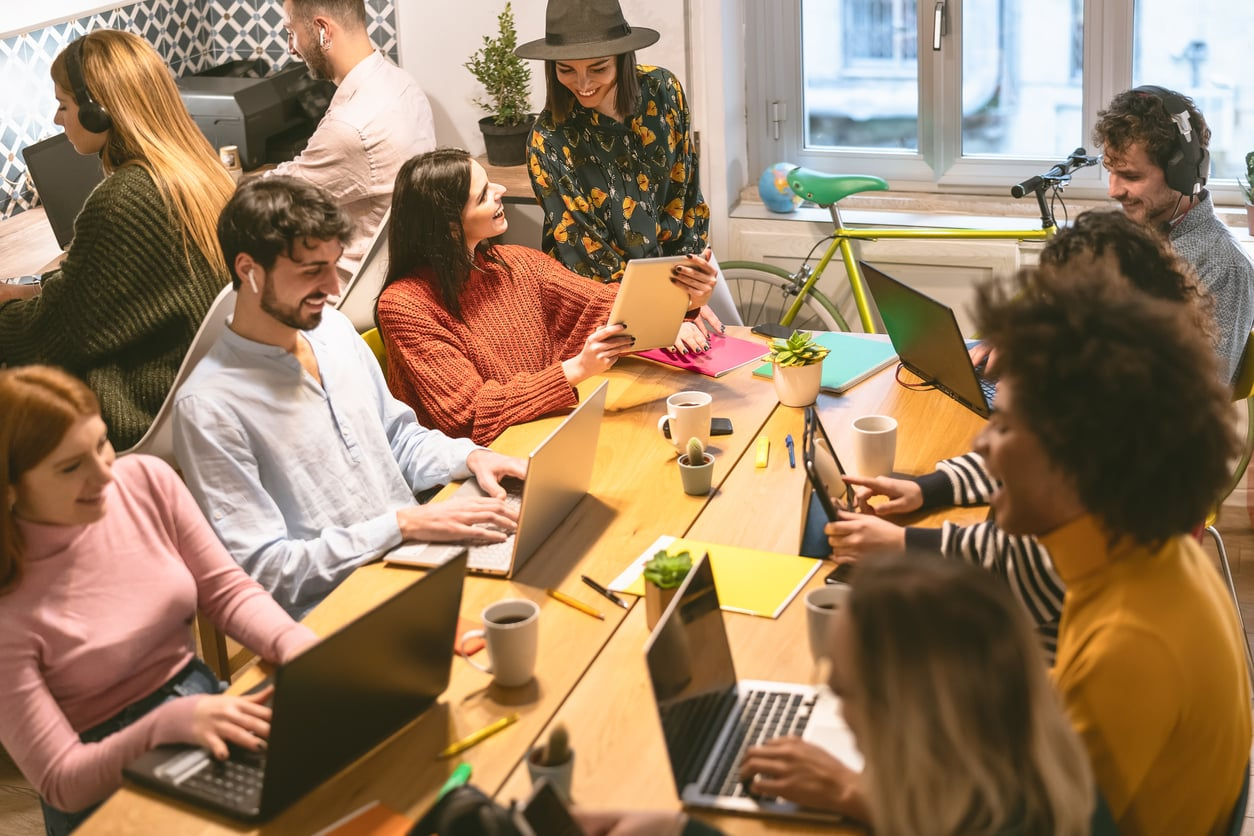 Group of happy and diverse Gen Z employees working in an office showing a concept of work-life balance.