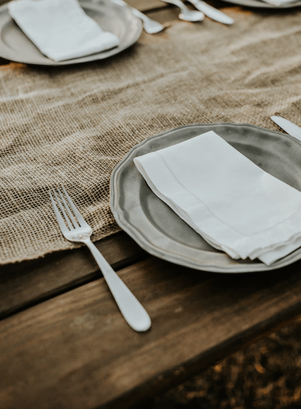 a rustic wooden table set with a burlap runner, pewter flatware, a grey scalloped edge plate and a white linen hemstitched napkin