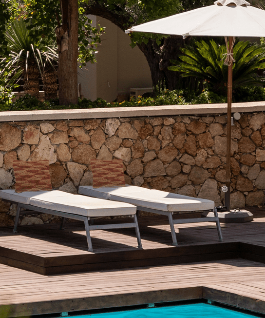 image of two lounge chairs and an umbrella next to a pool with a wooden deck