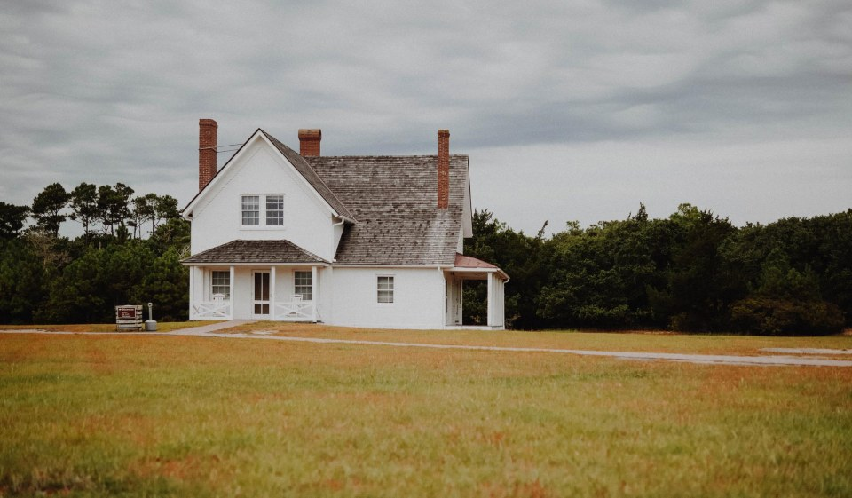 image of a white two gable farmhouse in a field of grass with trees in the background