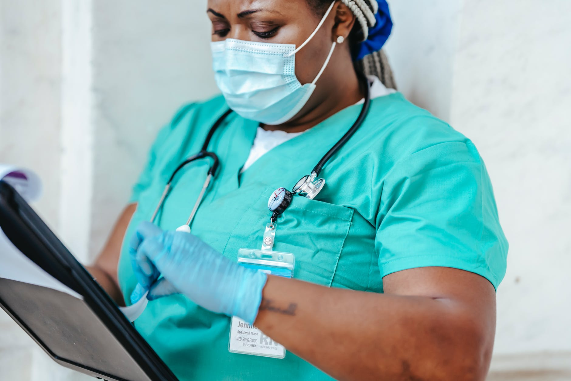 crop nurse in mask and gloves with papers