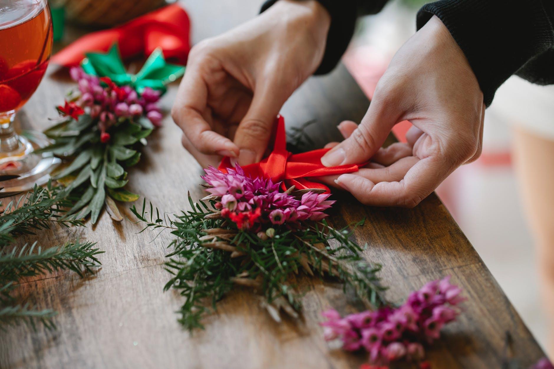 crop female florist making bow on fresh flower christmas bouquet