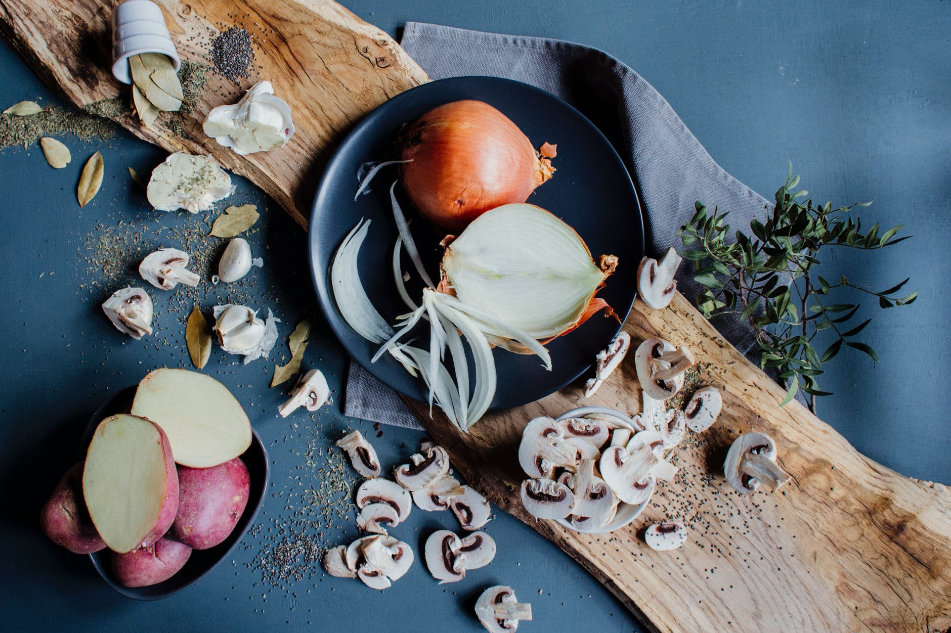 plate of raw onions placed on wooden board with potatoes and chopped mushrooms