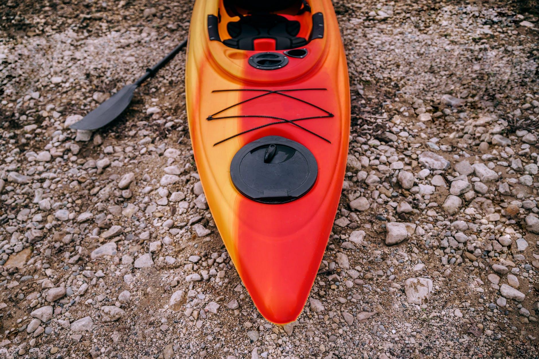 high angle photo of kayak on rocky ground