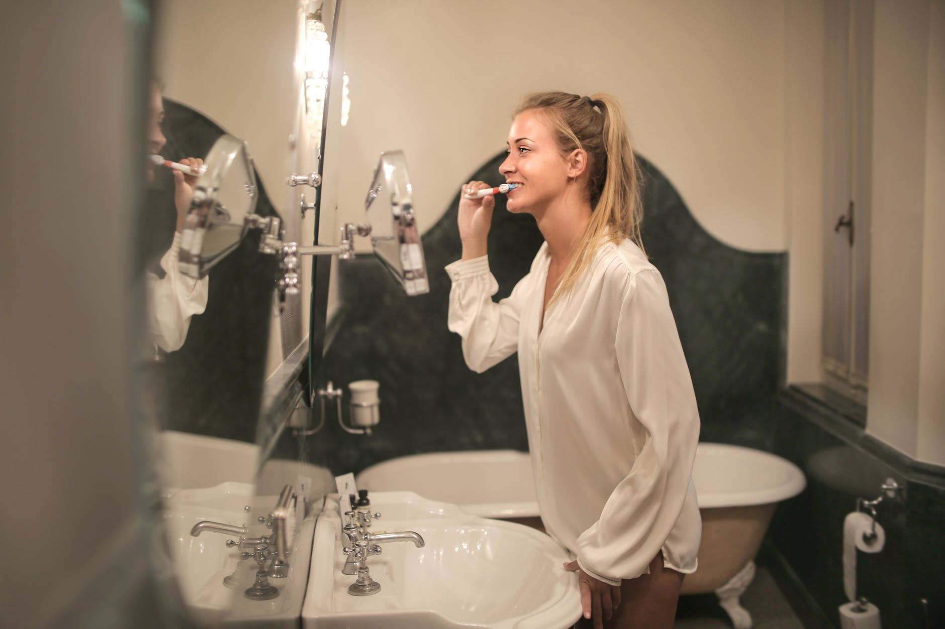 young woman cleaning teeth in bathroom