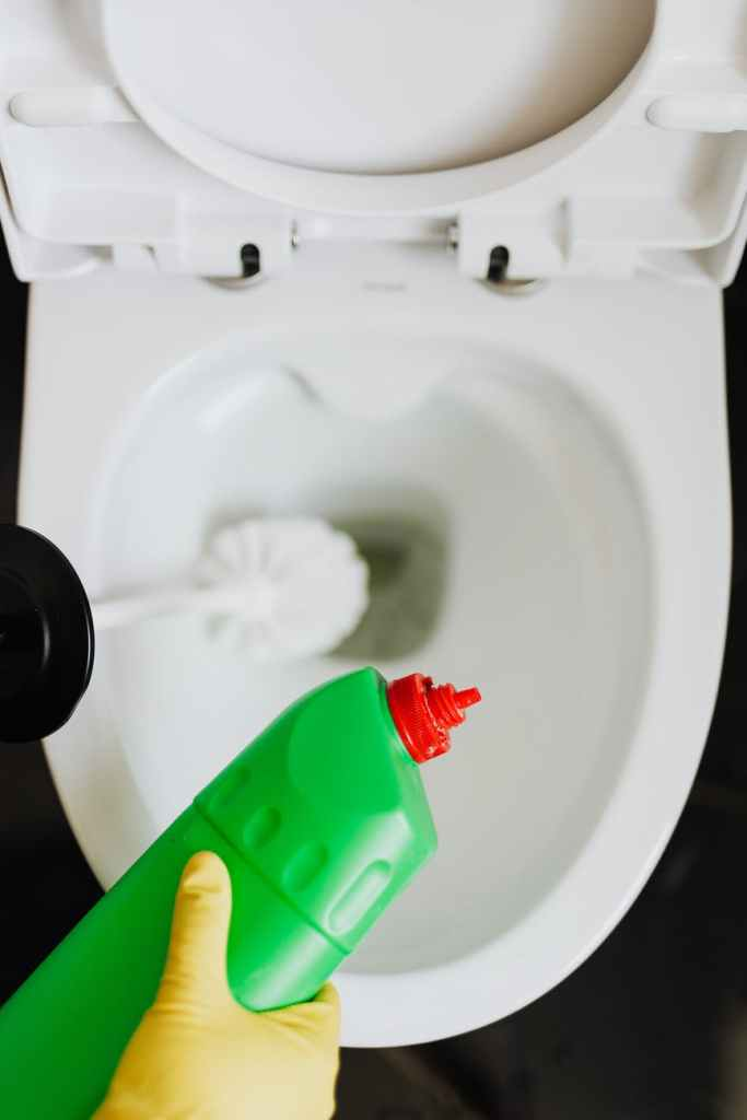 crop person cleaning toilet with detergent and brush