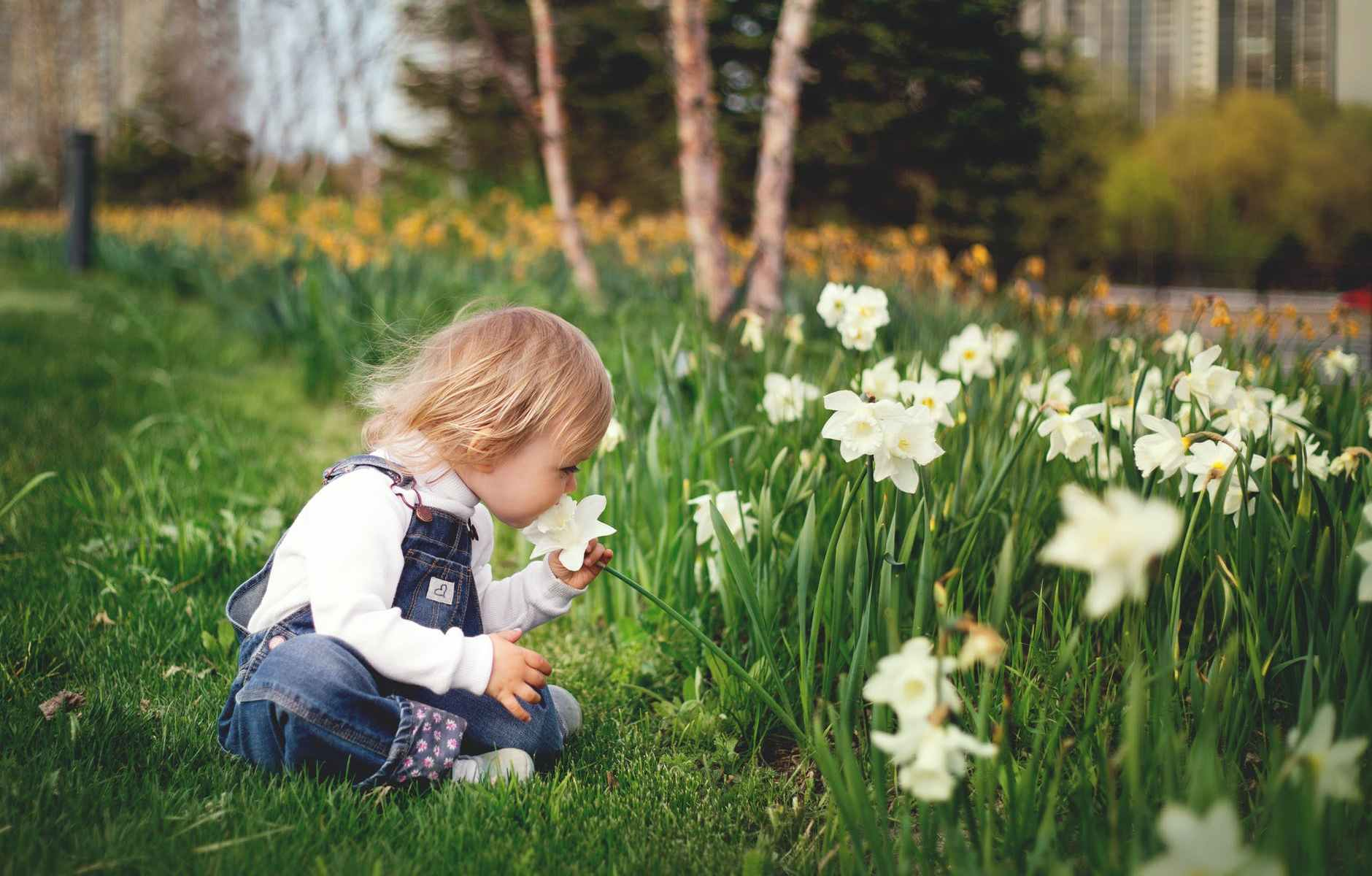 girl sitting on grass smelling white petaled flower