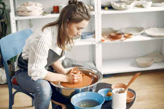 woman forming clay bowl on pottery wheel