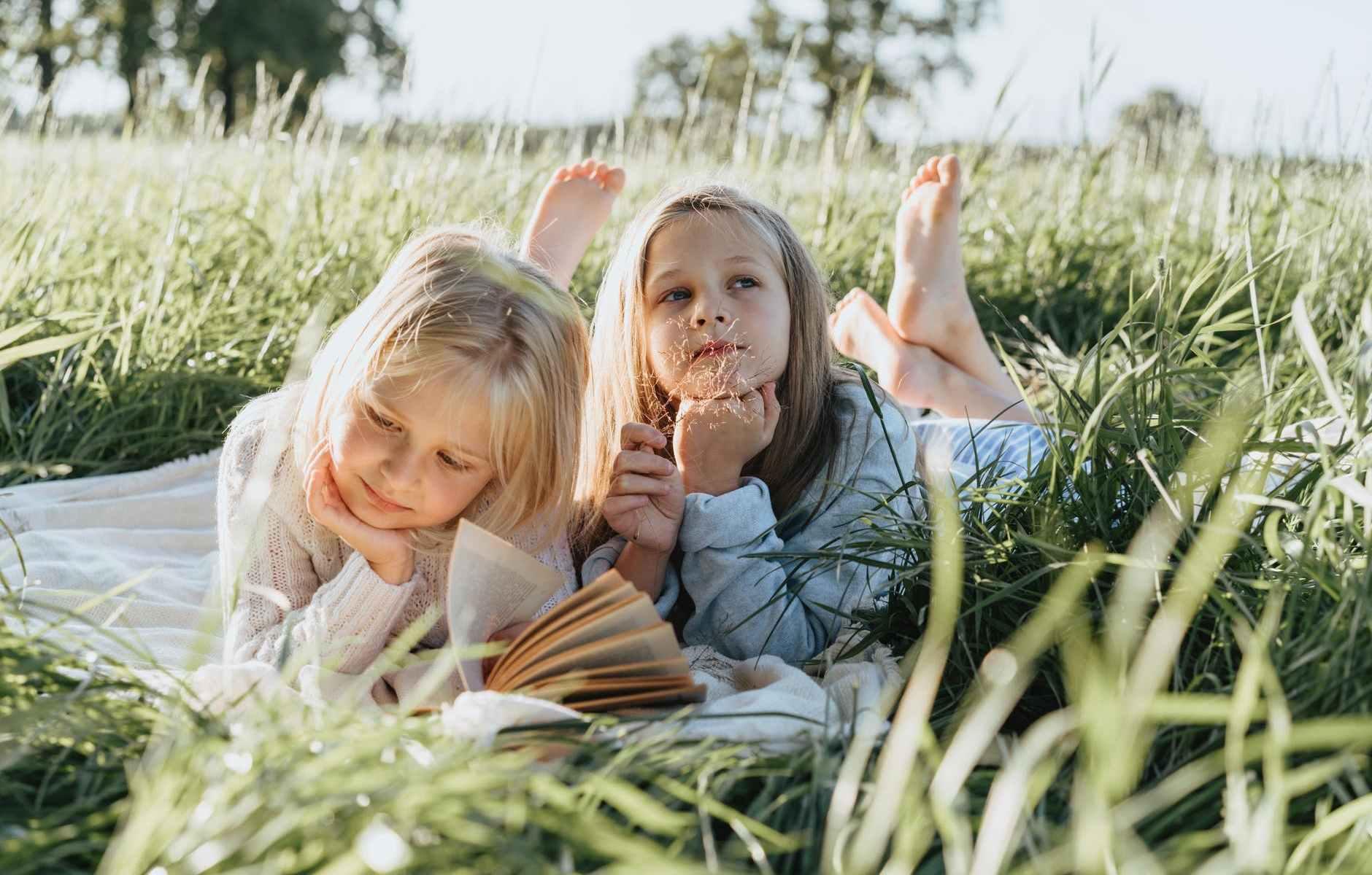 little girls lying on green grass field