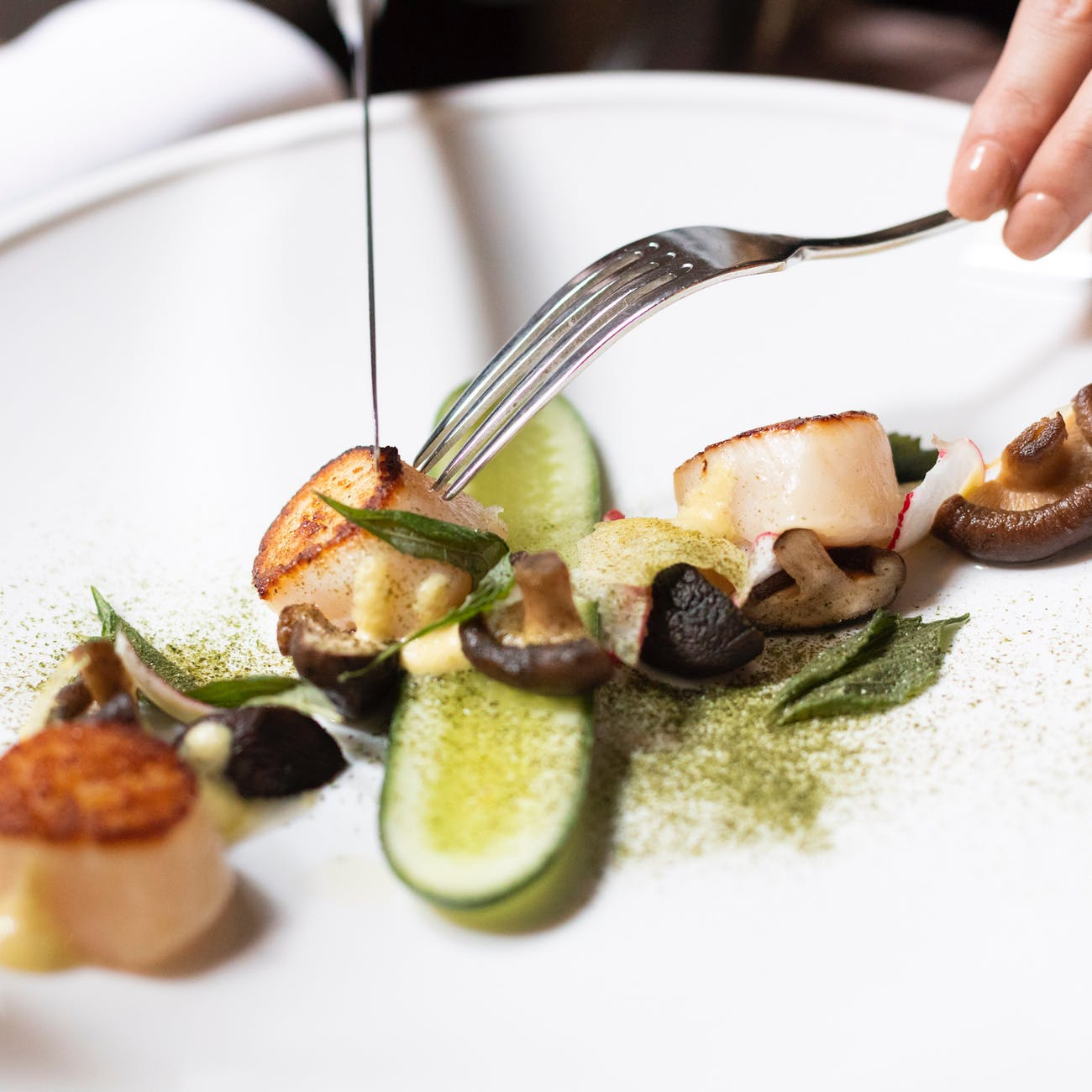 unrecognizable woman eating scallops with mushrooms and veggies in restaurant