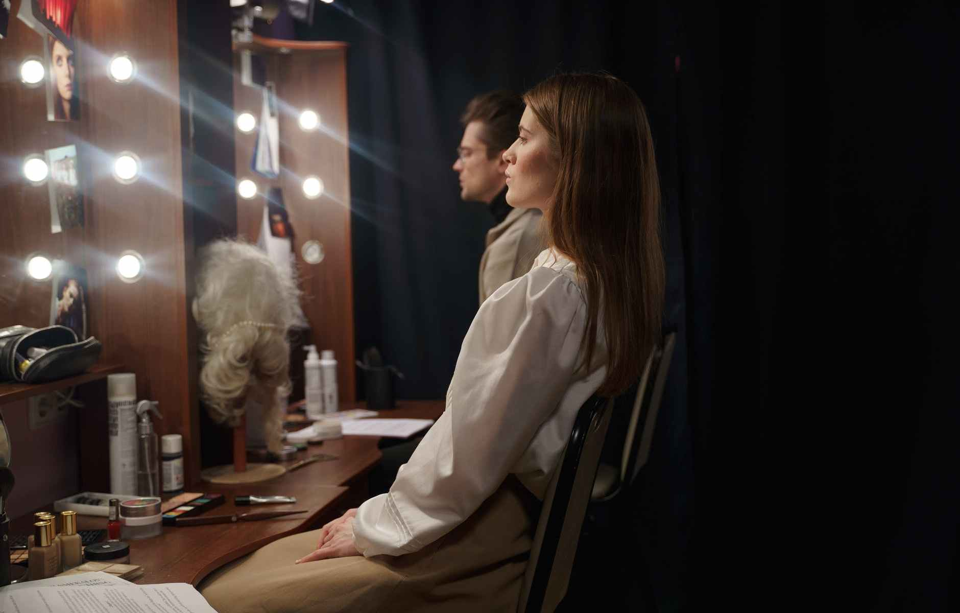 man and woman sitting infront of a mirror