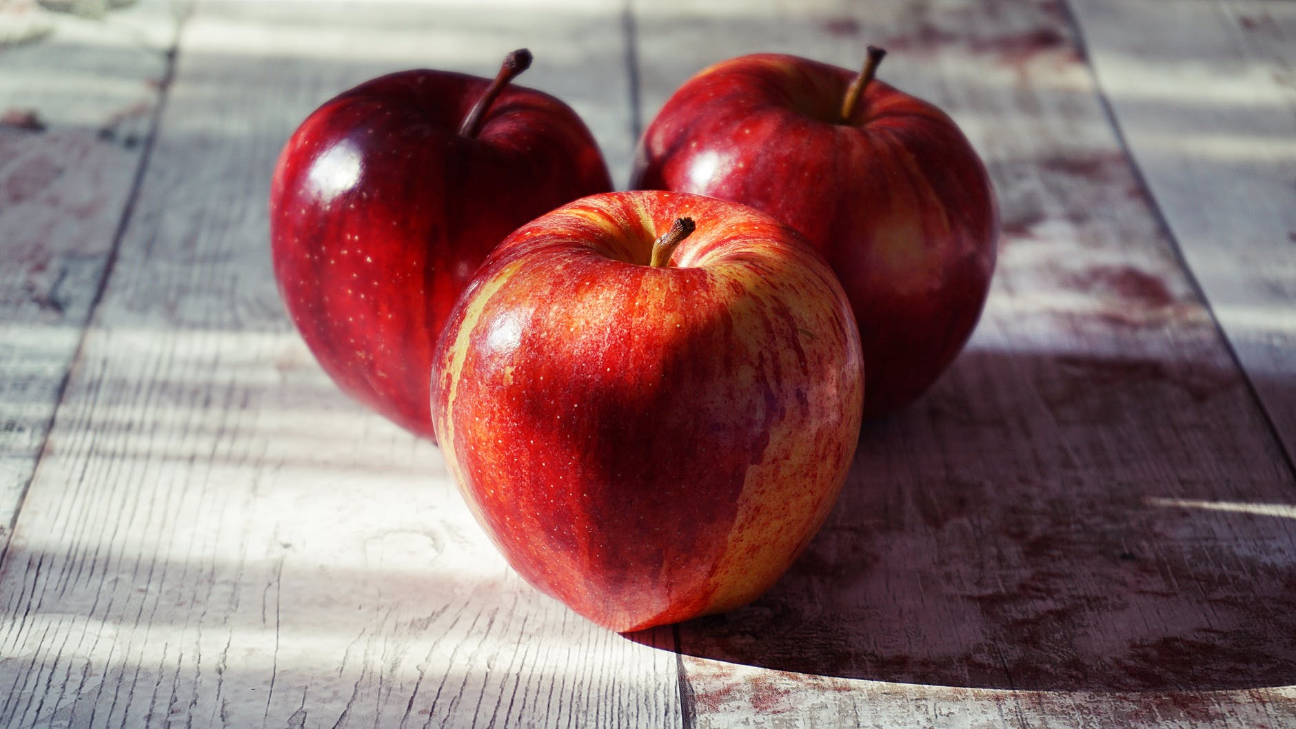 three red apples on wooden surface