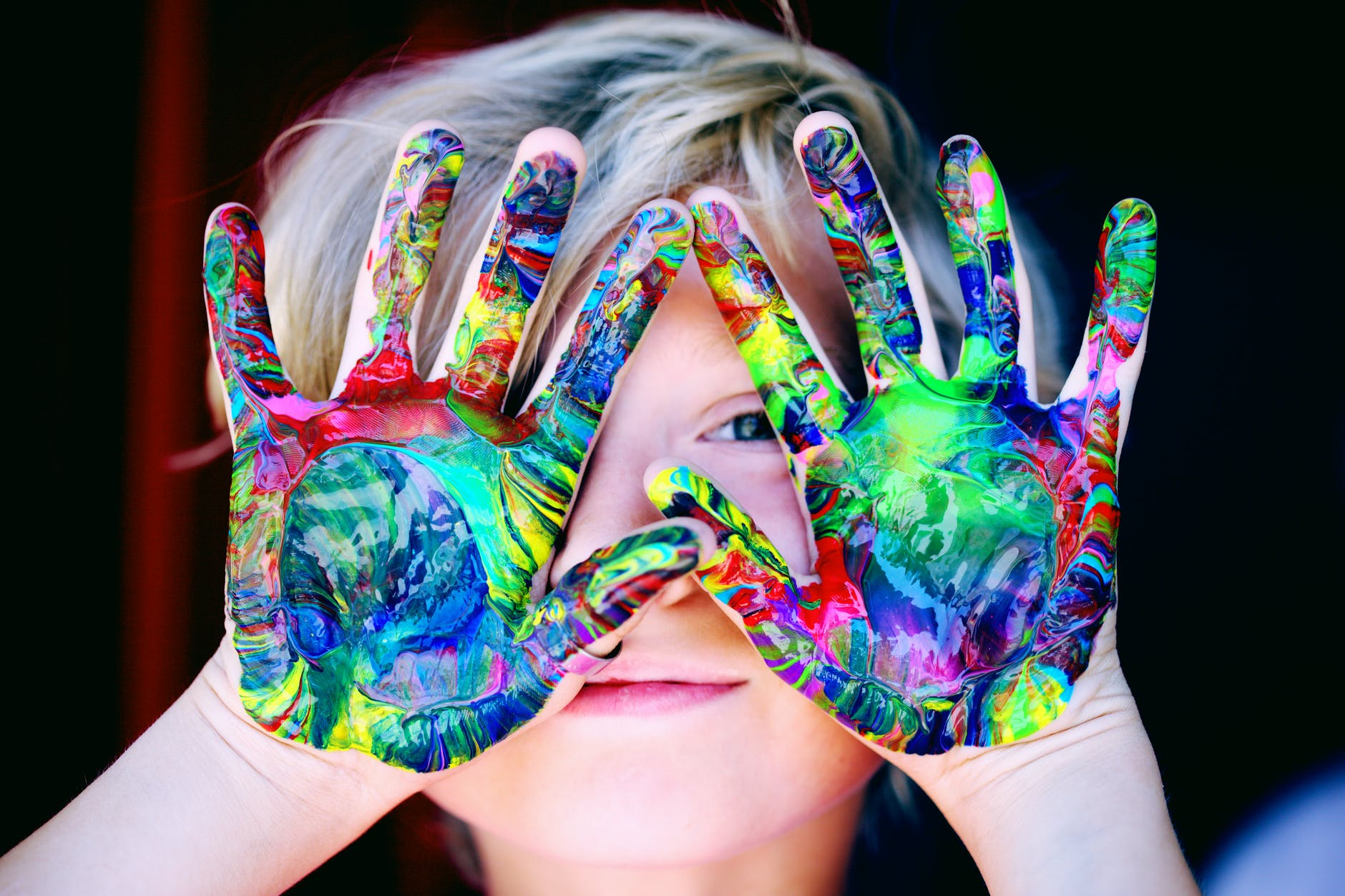 a kid with multicolored hand paint