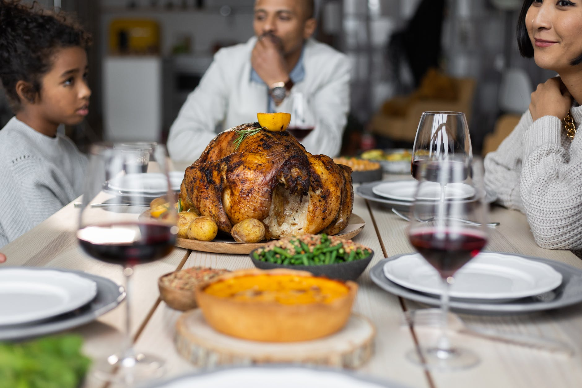 crop diverse people at table with turkey