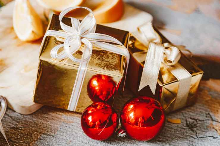 gold gift box with white ribbon besides red baubles