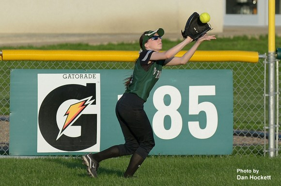 Photo by  Dan Hockett West Burlington – Notre Dame Right-fielder Courtney Coffin catches a long flyball in the first game of a doubleheader against Burlington Wednesday night in West Burlington. West Burlington – Notre Dame swept Burlington, 11-1, 5-3.