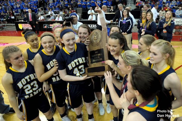Photo by Dan Hockett Notre Dame Teammates hold the '2014 Basketball State Champions' trophy after winning the Class 1A State Girls Championship Friday night at Wells Fargo Arena in Des Moines.