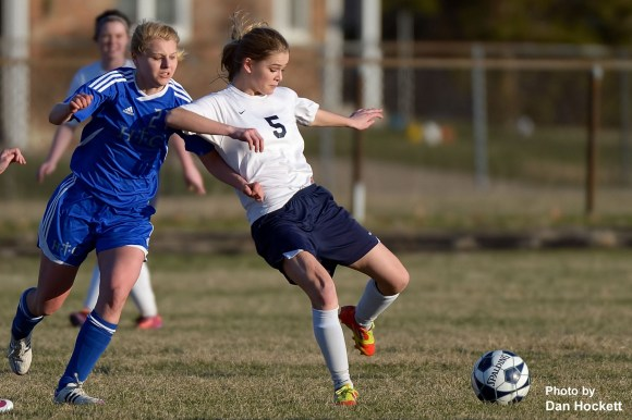Photo by Dan Hockett Notre Dame – West Burlington – Danville's Alex Ackerman (5) keeps the ball away from Holy Trinity's Maria Vonderhaar (27) during their soccer match Tuesday in Burlington. Lady Nikes defeated Holy Trinity, 2-1.