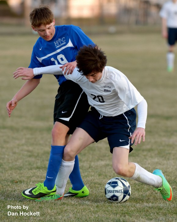Photo by Dan Hockett Notre Dame – West Burlington's Logan Patterson (20) fights to keep the ball away from Holy Trinity's Dylan Biegler (19) during their soccer match Tuesday in Burlington. Holy Trinity defeated NDWB, 1-0.
