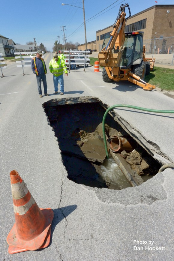 Photo by Dan Hockett Burlington and West Burlington City workers look at a large sink hole that formed in Mt. Pleasant Street between Leffler and Broadway Streets in West Burlington around noon Wednesday. The sink hole was caused by a leaking Burlington water main under the street. No one was hurt and no vehicles were damaged.