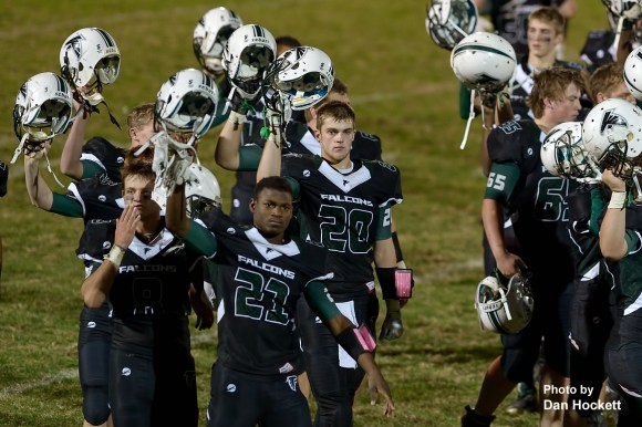 Photo by Dan Hockett West Burlington / Notre Dame Teammates raise helmets to thank fans after their game against Mediapolis Friday night in West Burlington. Mediapolis defeated WBND, 38-33.