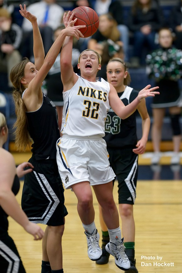 Photo by Dan Hockett Notre Dame's Taylor Hickey (32) is fouled by West Burlington's Aubrey Schmitt going to the basket Friday night in Burlington. Notre Dame defeated West Burlington, 100-38.