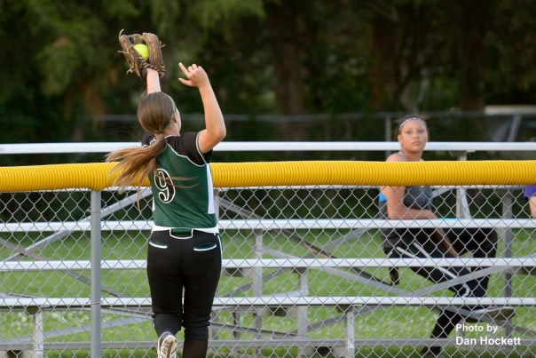 Photo by Dan Hockett West Burlington – Notre Dame Left Fielder Lexy Davis reaches over the fence to deny Highland's Kaytlin Chalupa a homerun in the fourth inning of Friday night's game in West Burlington. Highland defeated WBND, 4-2.