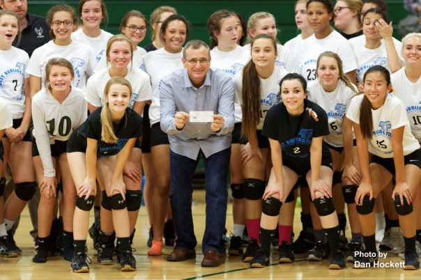 Photo by Dan Hockett Todd Baldridge (center) of 'Water Our Thirsty World' accepts check for $826.50 from the West Burlington High School Volleyball Team to build a well for a village in India. The Volleyball team held a fundraiser for the project.