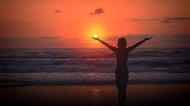 Celebrating life - A woman raises her arms at sunset on a deserted beach