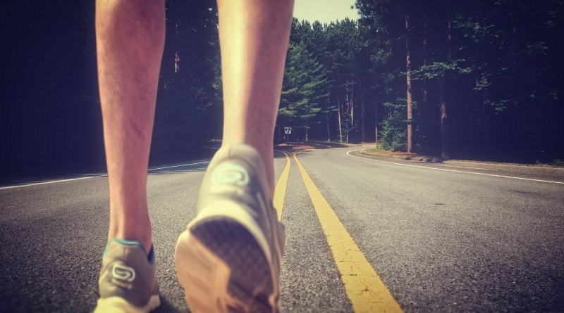 Feet of an athlete running on a deserted road - Training for fitness and healthy lifestyle