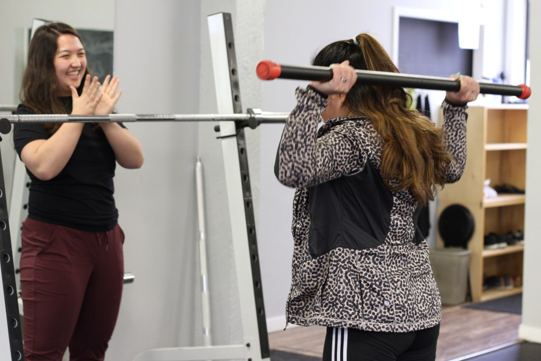 girl lifting bar, personal trainer kinesiologist clapping for her