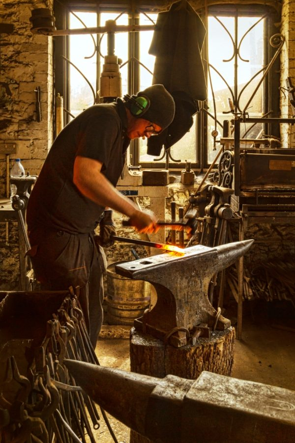 a blacksmith at Allerford Forge working at West Country Blacksmiths