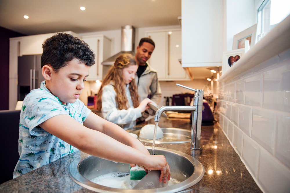 parent and children wash dishes