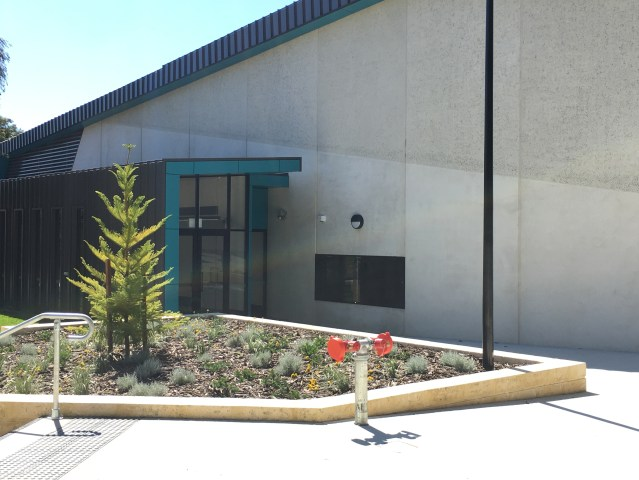 Grey building with a door for an entrance. A fire hydrant is in front of the building.