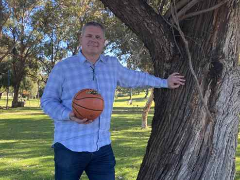 Andrew Vlahov holding a basketball, leaning against a tree.