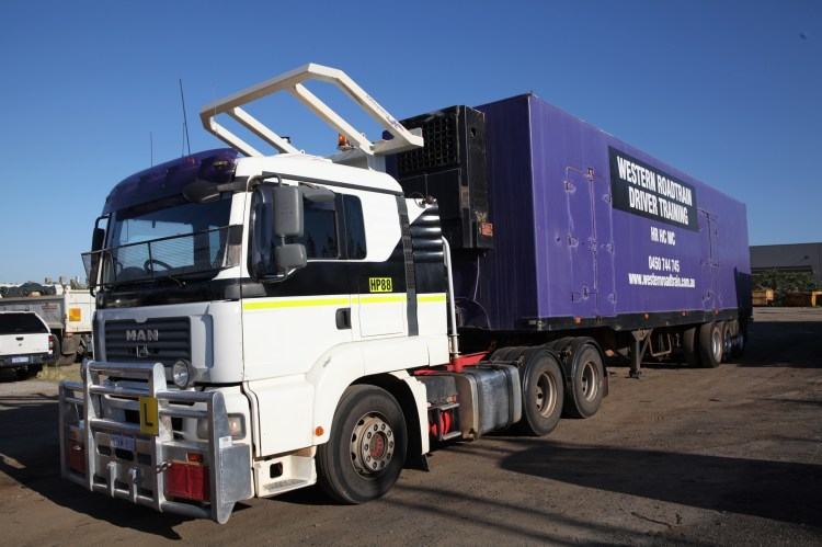 A Western Roadtrain Heavy Combination vehicle. This features the body of the truck plus one trailer. The branding is purple and represents Western Roadtrain, a Perth Truck Driving School.