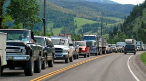Line of vehicles backed up on one side to a rural road in Montana