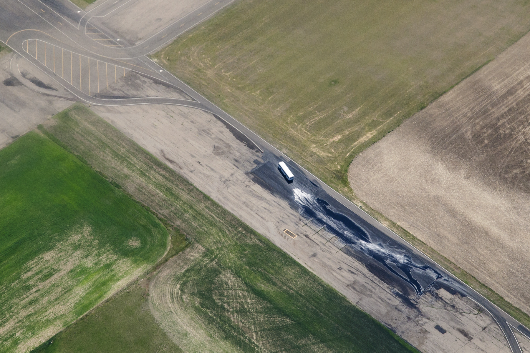 WTI Transcend aerial view. Passenger bus drives through section of test track that has been partially flooded with water,