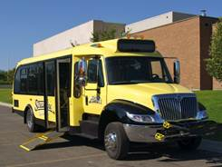 Streamline bus with front mounted bike rack and wheelchair loading ramp deployed.