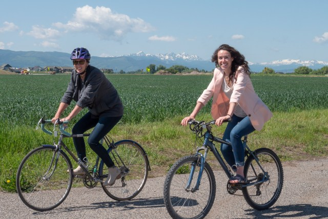 New staff members Dani Hess (Left) and Kelley Hall (Right) ride bikes outside WTI offices in Bozeman, MT