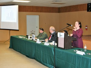 Natalie Villwock-Witte (at right) speaks at a podium. A presentation screen and two other seated panelists are shown.