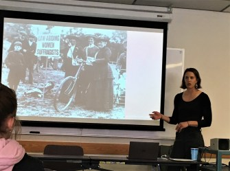 Dani Hess shows photos of women suffragettes during presentation on bicycle history