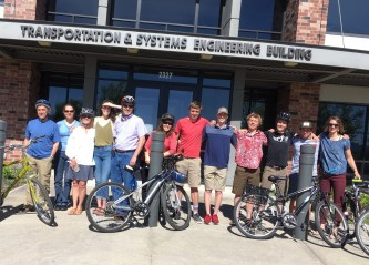 Twelve WTI and MDT staff members pose with bicycles in front of MSU transportation building.