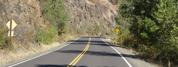 Cyclist travels along a curve on a mountainous highway