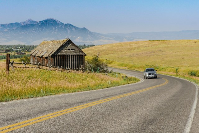 vehicle on two-lane rural highway near barn with mountains in background