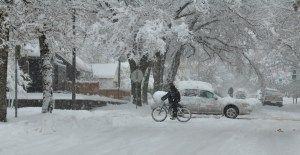 Bicyclist and car travel through neighborhood in heavy snow conditions