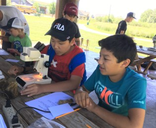 Students prepare to use a microscope during a camp activity 2019