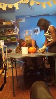 Xzavier Davis-Bilbo carves a pumpkin with sister Aruie Parris.